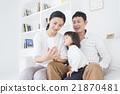 在生活方式沙发上操作智能手机的三个家庭 21870481