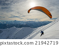 Paraglider launching from snowy slope 21942719