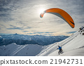 Paraglider launching from snowy slope 21942731