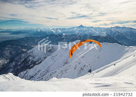 Paraglider launching from snowy slope 21942732