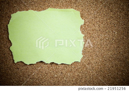 Crumpled yellow sticky note on cork board. 21951256