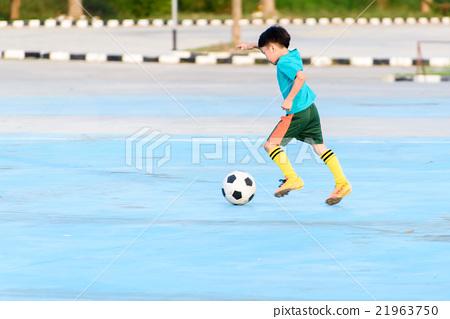 Boy play football on the blue concrete floor. 21963750