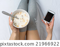 Woman eating cereals and texting in bed 21966922
