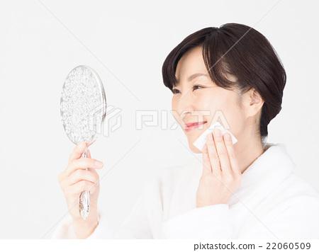 웃는 얼굴로 메이크업을하는 가운데 여성 22060509