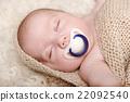Sleeping baby lying on a blanket 22092540