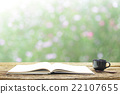 Notebook  and coffee in black cup on wooden table 22107655
