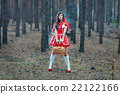 Beautiful girl in a red raincoat alone in the woods. 22122166