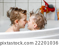 Two little boys playing together in bathtub 22201036