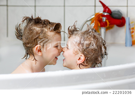Stock Photo: Two little boys playing together in bathtub