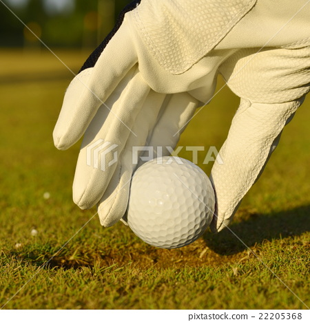 Stock Photo: green field and white golf ball sanset