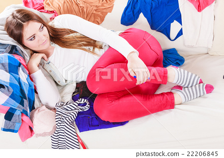 Woman lying on clothes. Mess and disorder. 22206845