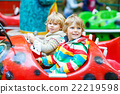 Two little kid boys on carousel in amusement park 22219598