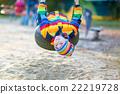 Little kid boy swinging on playground outdoors 22219728