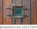Window with grate in old wooden door 22222304