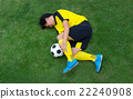 Football player lying injured on the pitch. 22240908