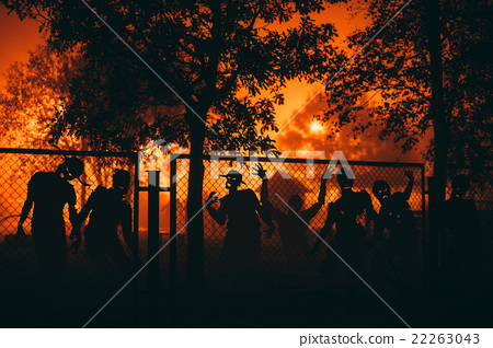 Several zombie behind a mesh fence. 22263043