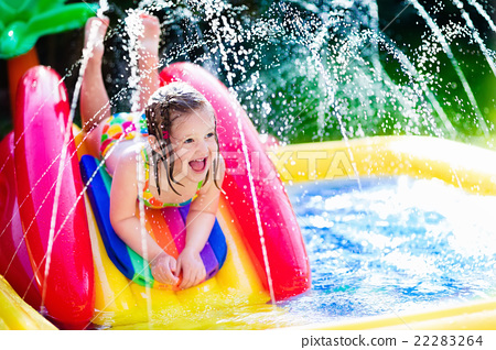 Stock Photo: Little girl in inflatable garden swimming pool