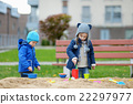 Two kids playing in a sandbox 22297977
