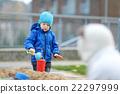 Two kids playing in a sandbox 22297999