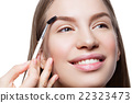 Woman correcting eyebrows form 22323473