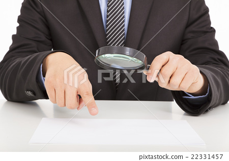 Businessman pointing through a magnifying glass  22331457