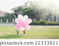 child with many balloons running in the park  22333621