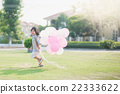 child with many balloons running in the park  22333622