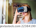 Woman wearing virtual reality goggles standing in 22364190