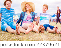 Teenagers at summer music festival, sitting on the 22379621