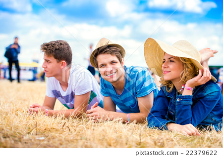 Teenagers at summer music festival, lying on the 22379622