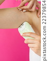 Woman epilates her armpit with an epilator 22379854