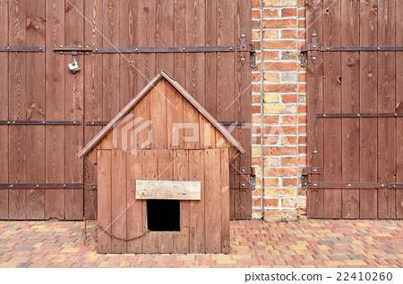 Wooden kennel in front of a barn. 22410260