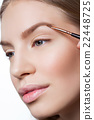 Woman correcting eyebrows form 22448725