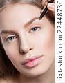 Woman correcting eyebrows form 22448736
