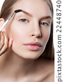 Woman correcting eyebrows form 22448740