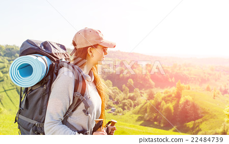 Young hiker woman with backpack walking on hills 22484739