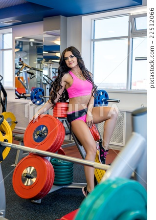 In gym. Beautiful brunette posing with barbell 22512066