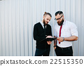 Two bearded businessman signing documents 22515350
