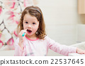Little girl in pink pyjamas in bathroom brushing 22537645