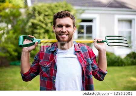 Smiling man carrying rake while standing in yard 22551003