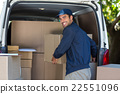 Happy delivery man loading cardboard box in van 22551096