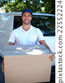 Portrait of happy delivery man holding cardboard box 22552224