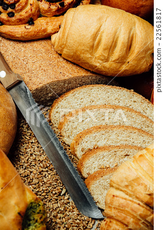 Sliced bread and knife on wooden table 22561817