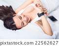 Nice smiling  woman resting in bed   22562627