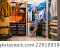 Young woman choosing clothes for husband 22619939
