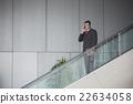 Indian businessman standing on an escalator. 22634058