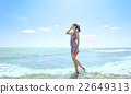 Young  woman standing in sea waves  22649313