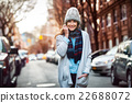smiling woman walking on city street 22688072