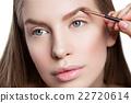 Woman correcting eyebrows form 22720614