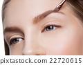 Woman correcting eyebrows form 22720615